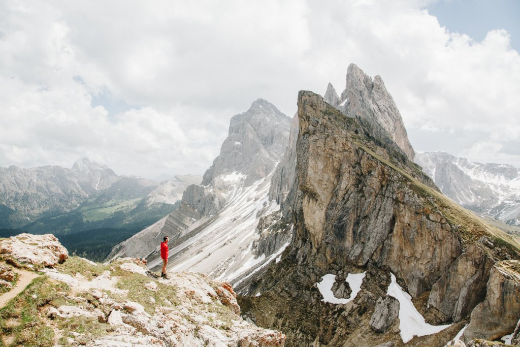 man stands in front of dramatic jagged peaks in the Dolomites
