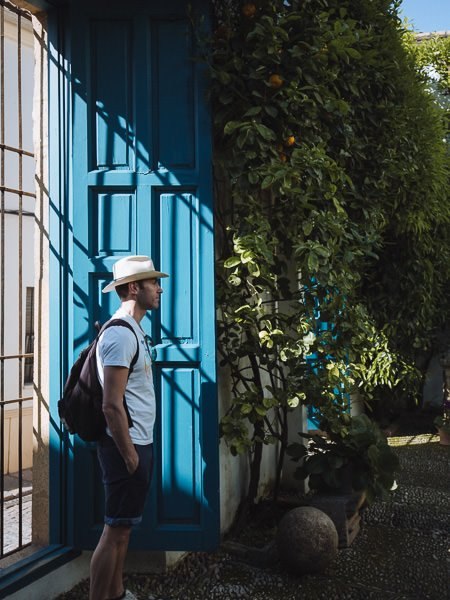 Man stands in front of blue door in patio garden
