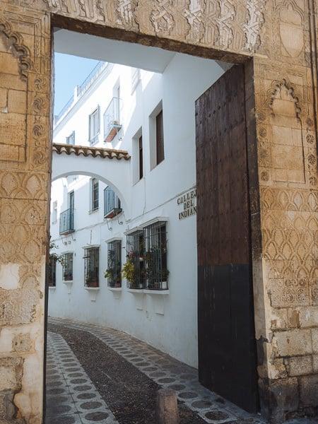 Etched stone entrance to whitewashed laneway in Córdoba