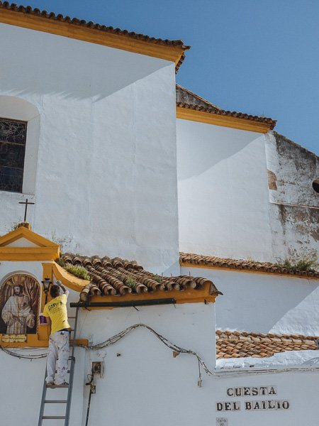 Man on ladder paints frame of religion image on a white church.