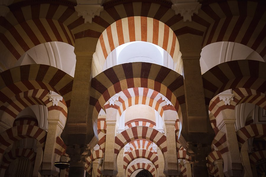 A series of red and yellow arches inside the Córdoba mosque prayer hall