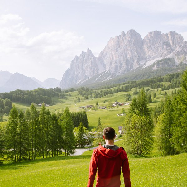 bright green field dotted with huts in the Italian Dolomites with rocky mountains framing the background