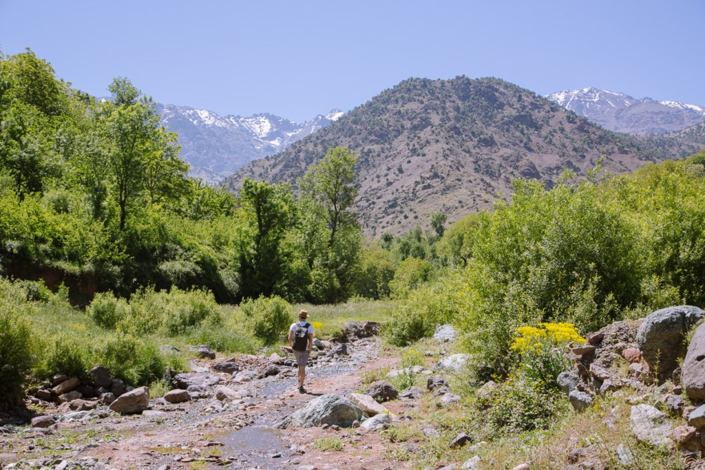 walking along a valley floor with a river and snow capped mountains in the distance.