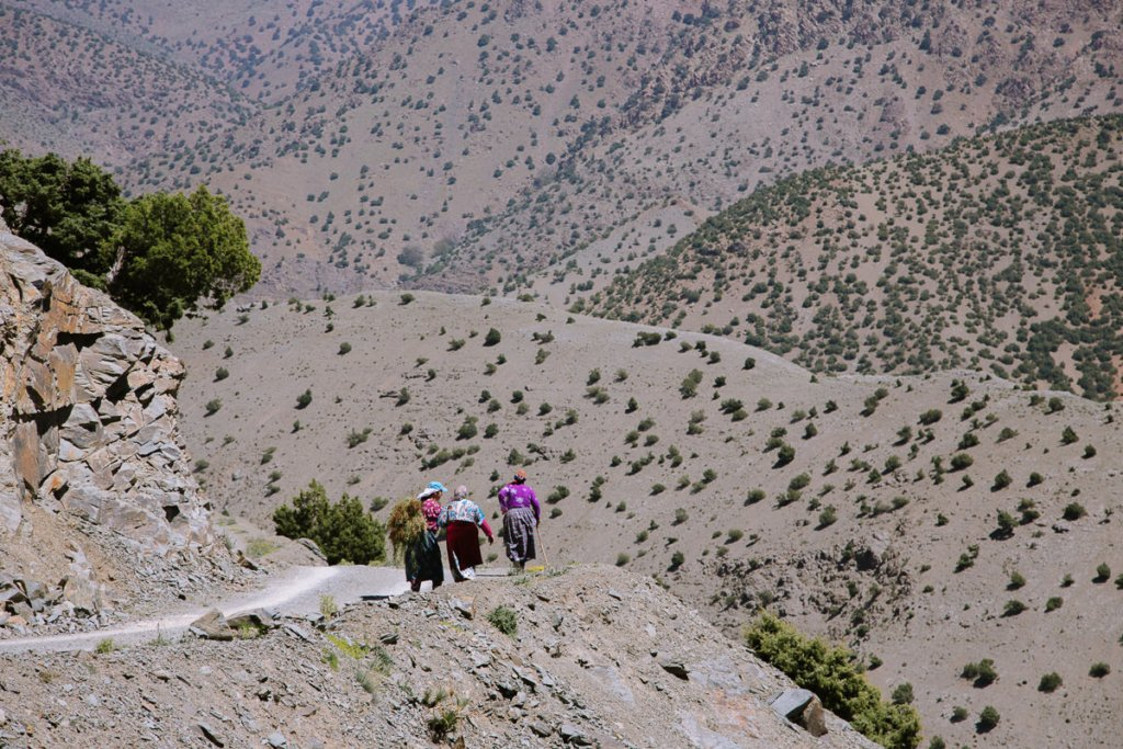 Berber women in colourful outfits walk up a steep mountain road
