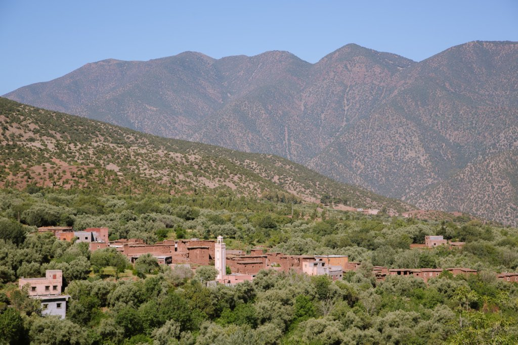 A small stone mosque surrounded by green trees under tall mountains