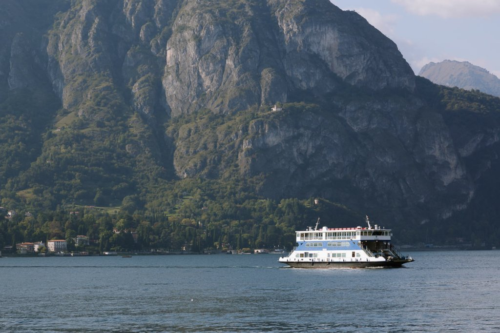 large ferry on a lake with a tall mountain in the background