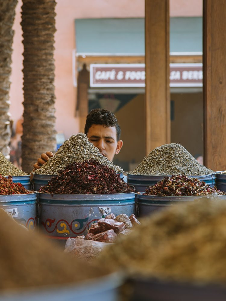 spices piled high in front of a stall holder, Marrakech