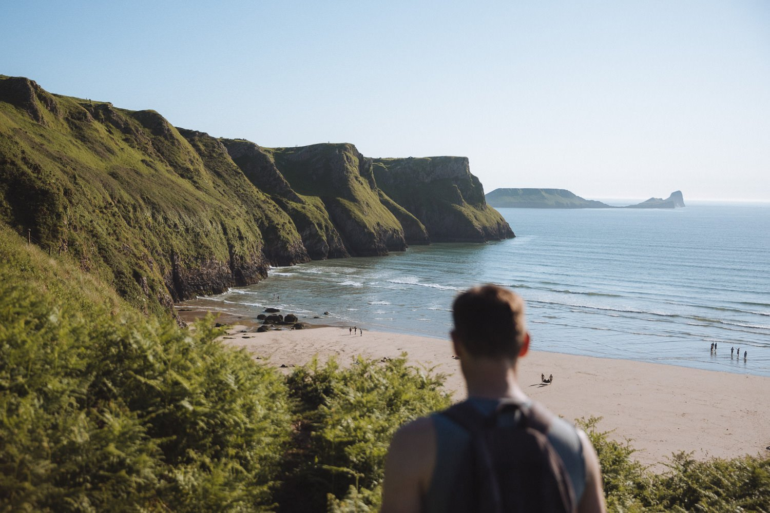 standing in front of a wide sandy beach with cliffs reaching the sea