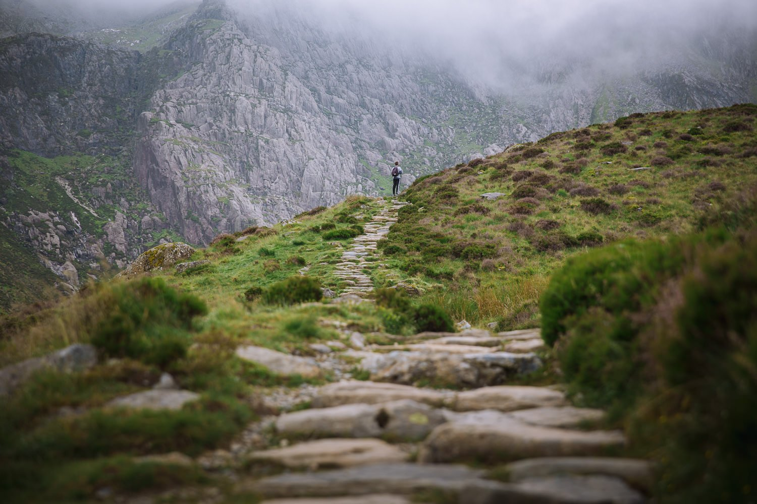 walking up a rocky hiking trail with a wall of mountains in the background