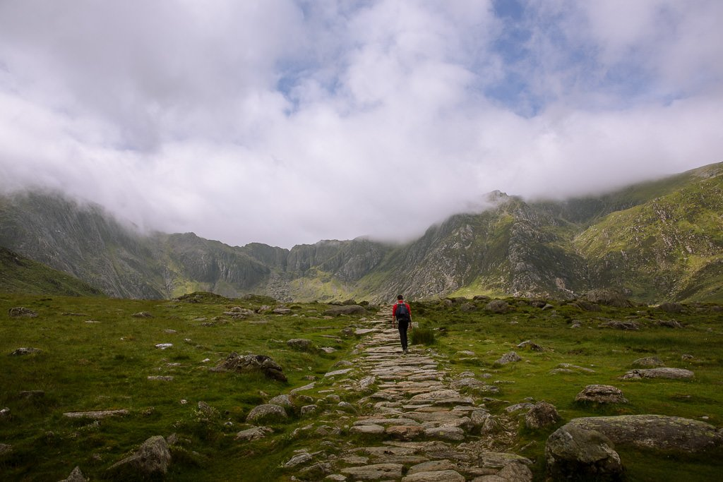 walking on a rocky path with misty cloud around mountains