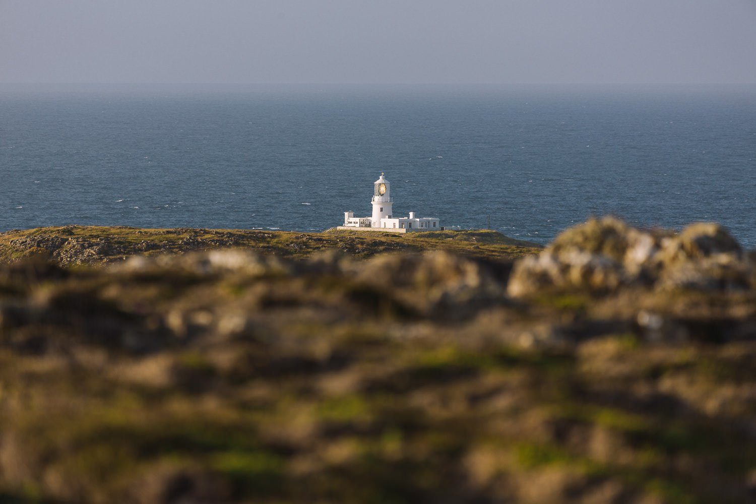 white lighthouse in front of the sea