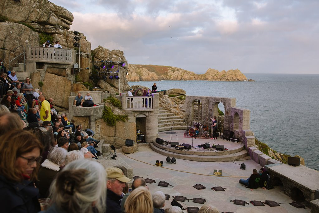 a theatre cut into a cliff on the side of the sea