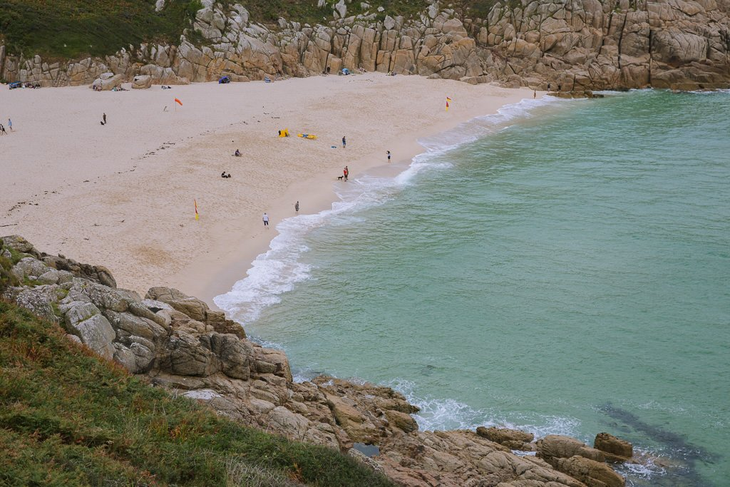 a triangular shaped beach with granite cliffs on the side